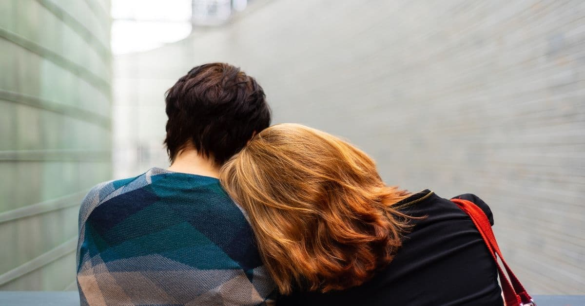 Image seen from the back, a light haired woman laying her head on the shoulder of a dark haired person