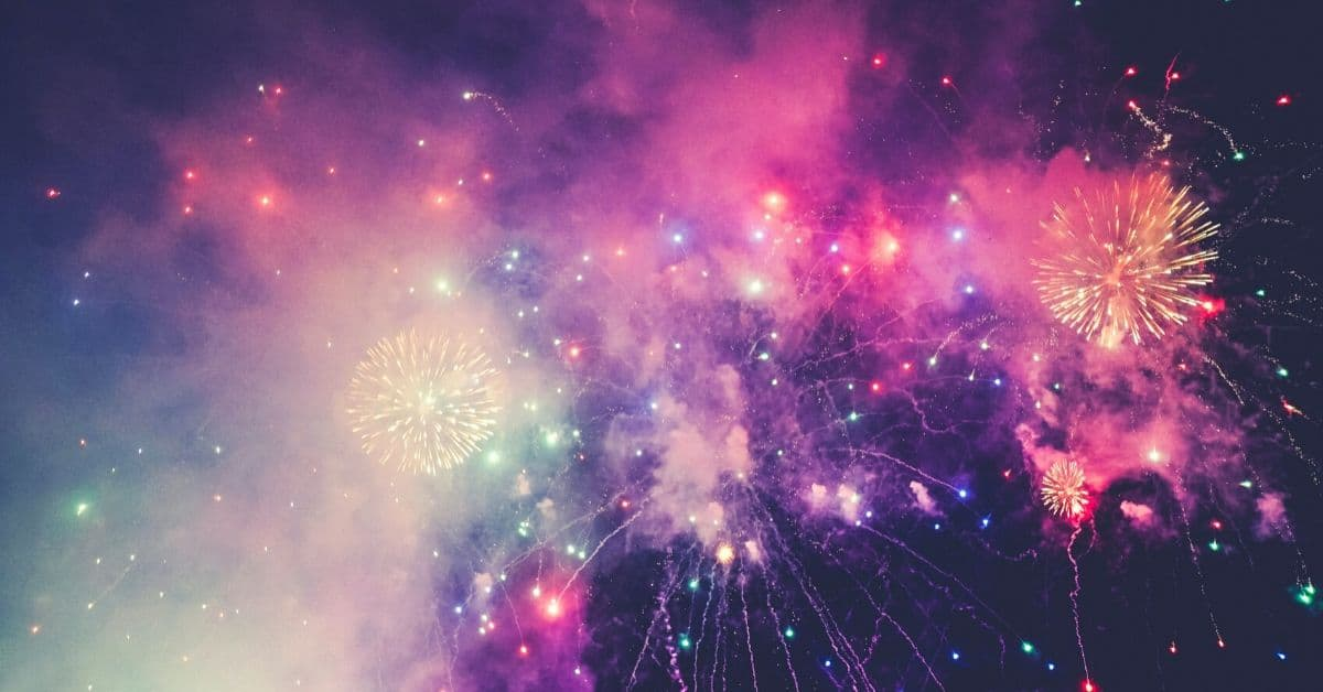Pink, blue, and purple fireworks with light smoke in a night sky
