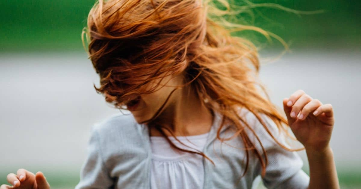 A young girl in a white top shaking her head from side to side, her hair covers her face
