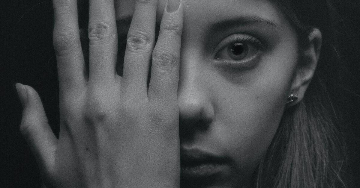 Black and white photo of a young woman covering the right side of her face with her hand