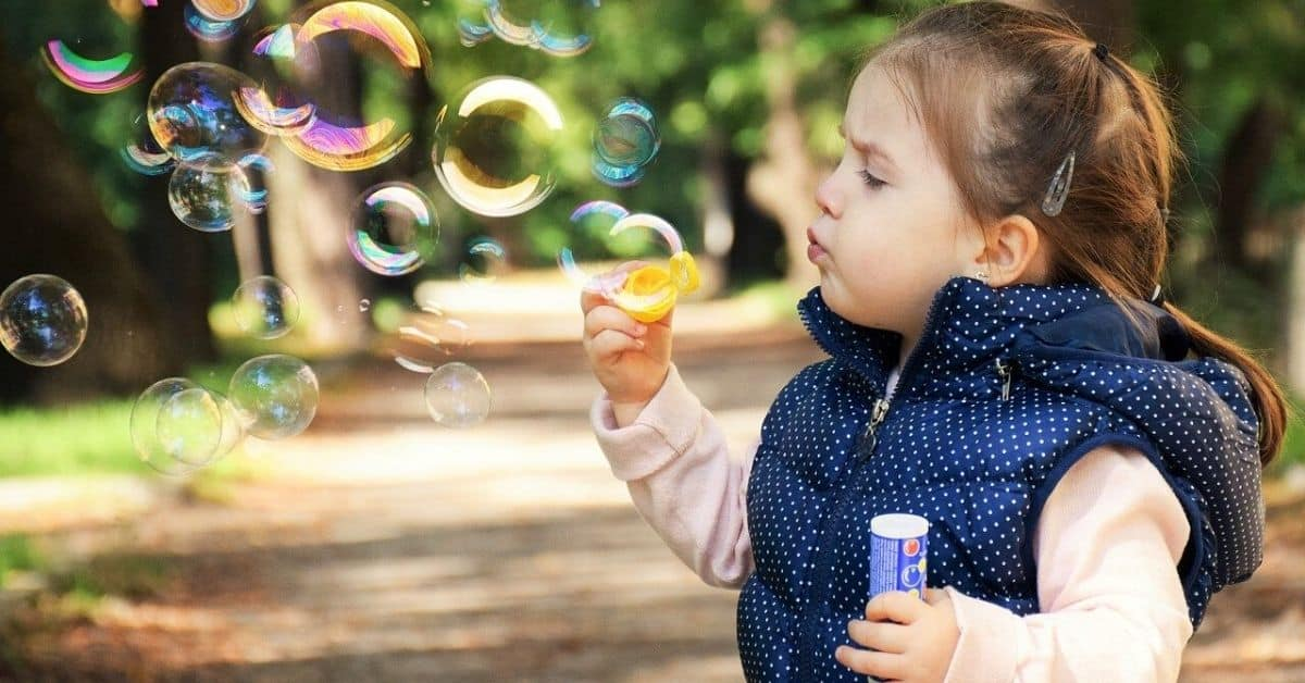 A toddler with long dark hair, wearing a pink long-sleeved shirt and a blue and white dotted puffer vest, blowing bubbles
