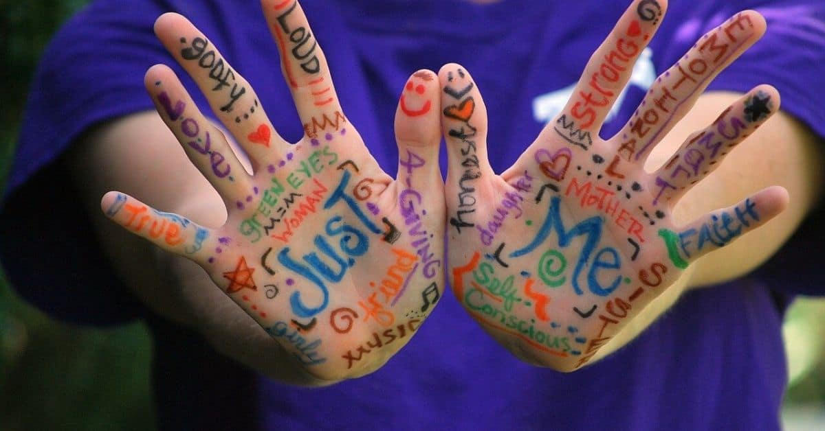 """Two outstretched palms with words written all over them. The phrase """"Just Me"""" stands out among words like """"mother"""", """"daughter"""", """"sister"""", """"music"""" and others"""