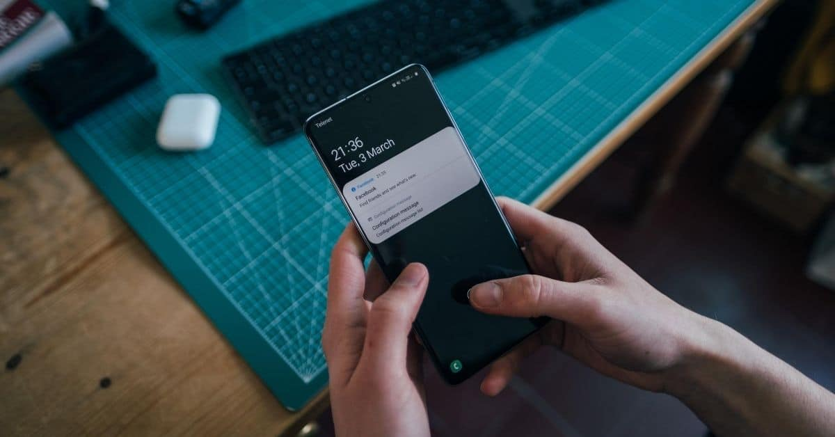 two hands holding a black smartphone showing two notifications with a green table and black keyboard in the background