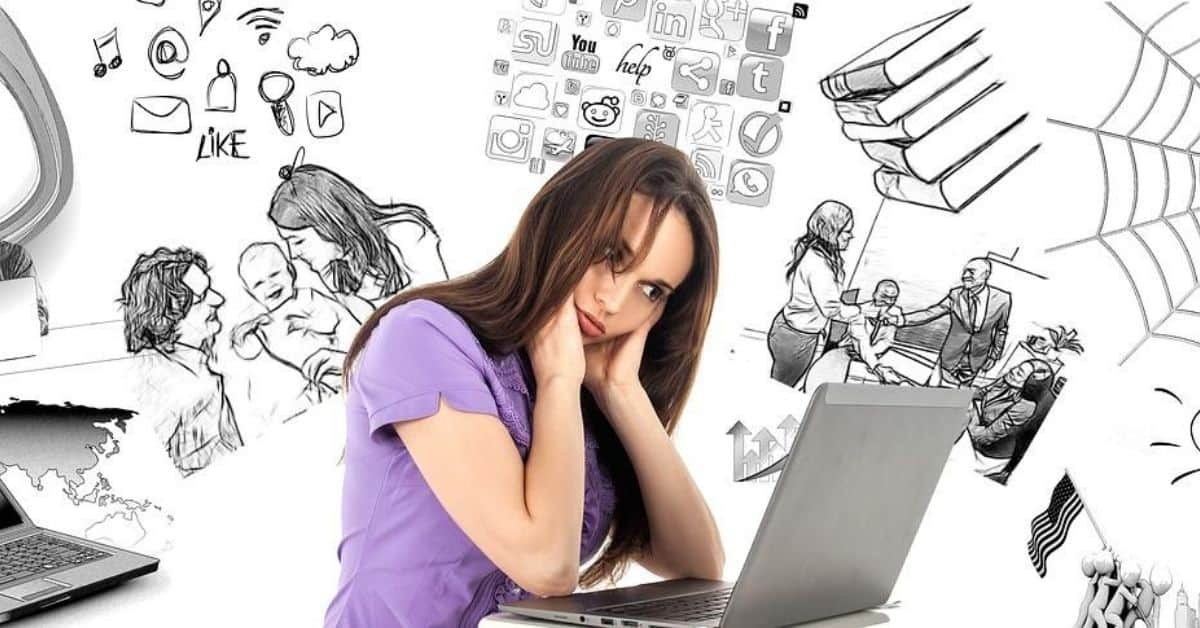 A dark haired woman in a purple tshirt sits looking at her laptop looking overwhelmed. Behind and around her are drawings of family and social interactions, social media, and other things she is thinking about