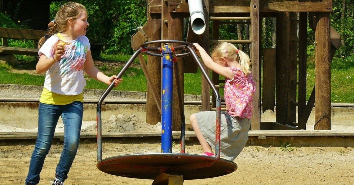 Two little blonde girls playing on a merry-go-round on a playground