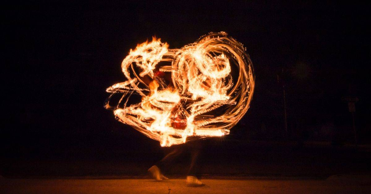 A fire dancer on a beach at night. Their feet are visible beneath multiple light echoes of their fire poi balls.