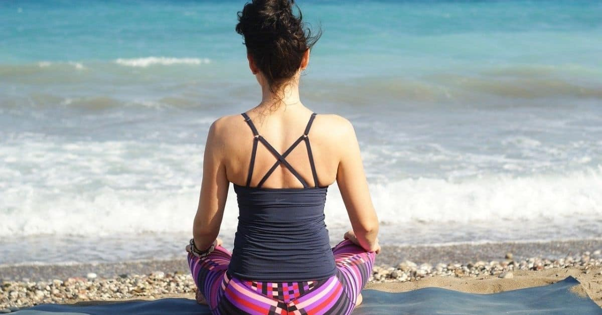 A woman wearing a strappy grey tank top and pink striped leggings is seen from the back sitting on a beach