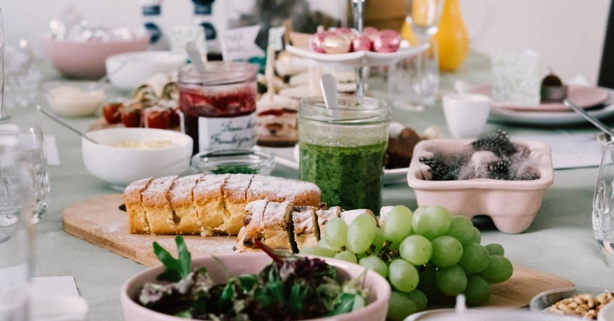 A table laid with foods including bread, berries, grapes, salad, jam, and more.