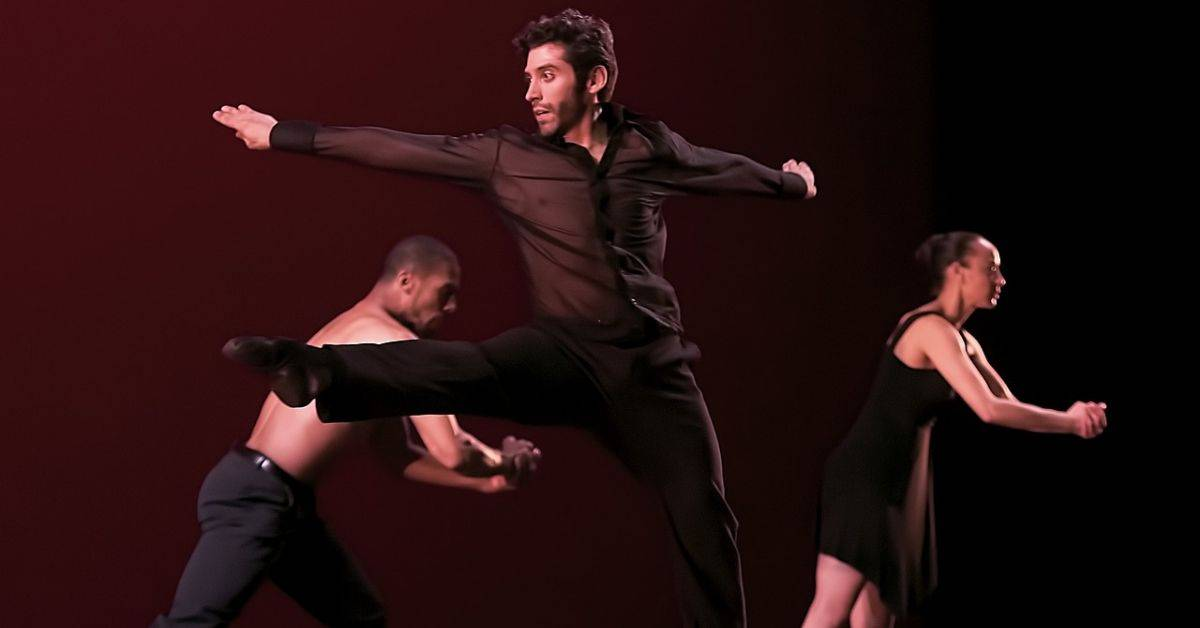 Three dancers wearing black, one in front in mid turn