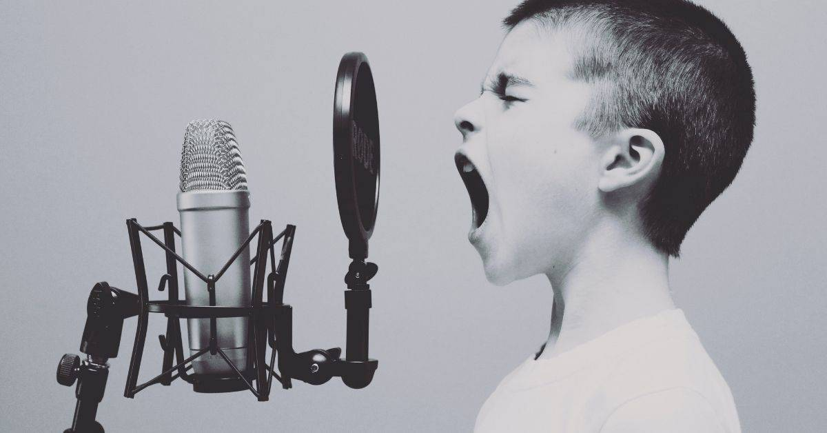 Black and white picture of a boy singing loudly into a microphone.