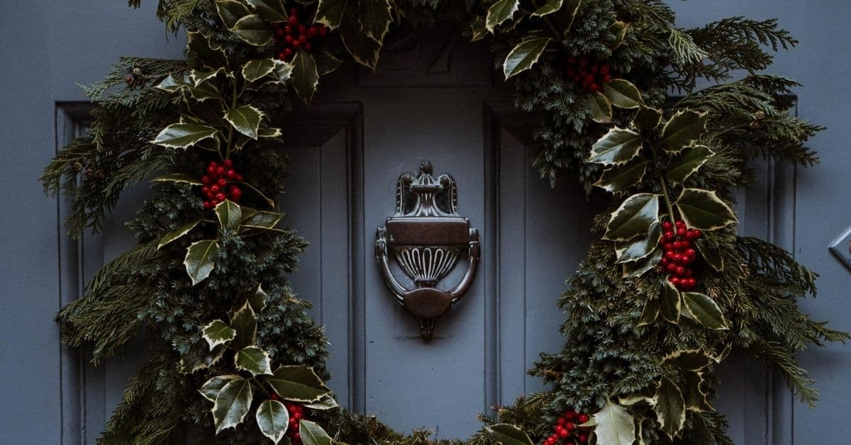 A wreath of green pine and holly with a few red holly berries against a blue door with a dark metal knocker