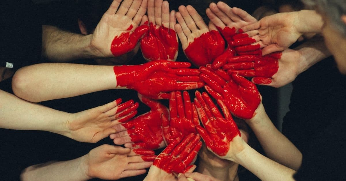 A red heart painted across the palms of many hands together