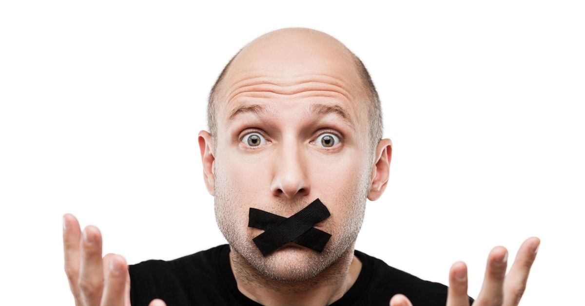 A balding man with a cross of black tape over his mouth, looking helpless