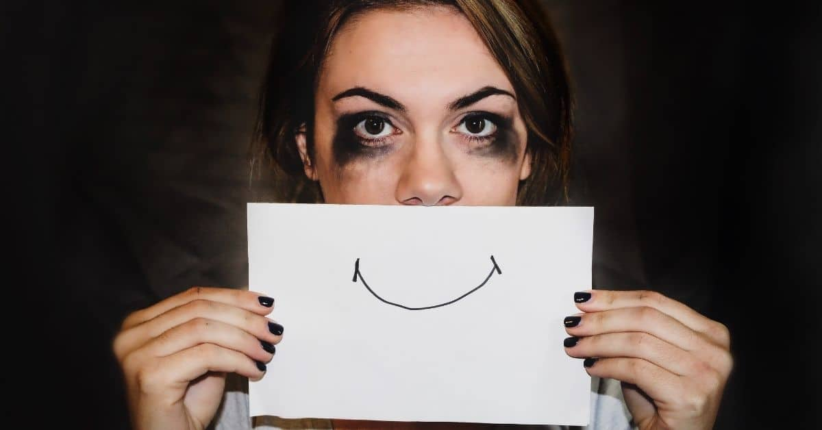 Woman with smudged eye makeup that looks like she's been crying holding a piece of paper with a pen-drawn smile in front of her face.