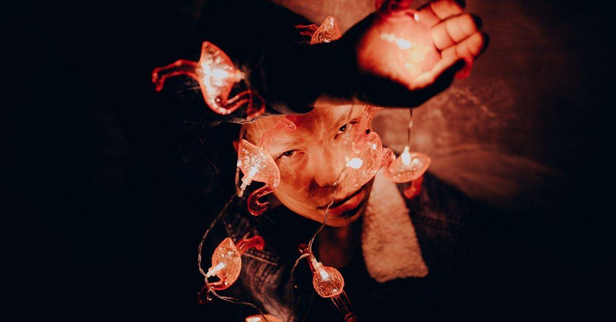 A person in a dark room, their facr partly lit by a string of lights