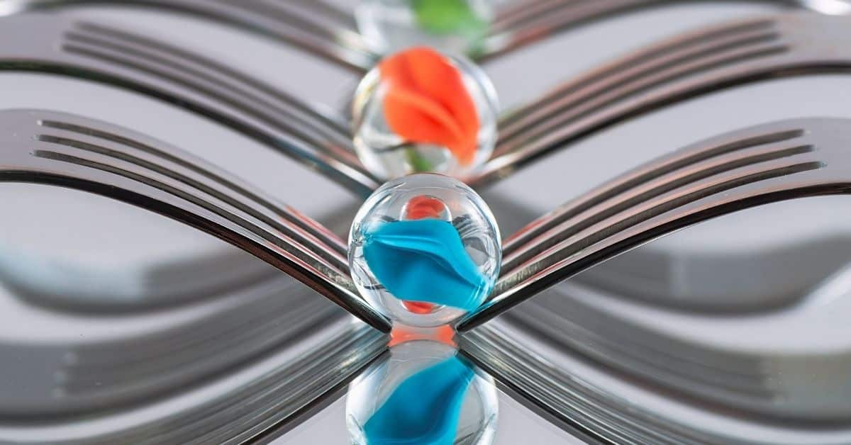 A line of clear marbles with multicolored swirls in their centers sitting on silver infinity symbols