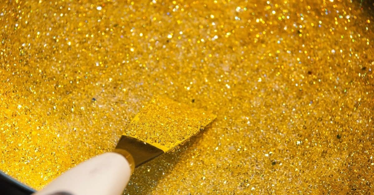 A pile of gold glitter with a palette knife in it