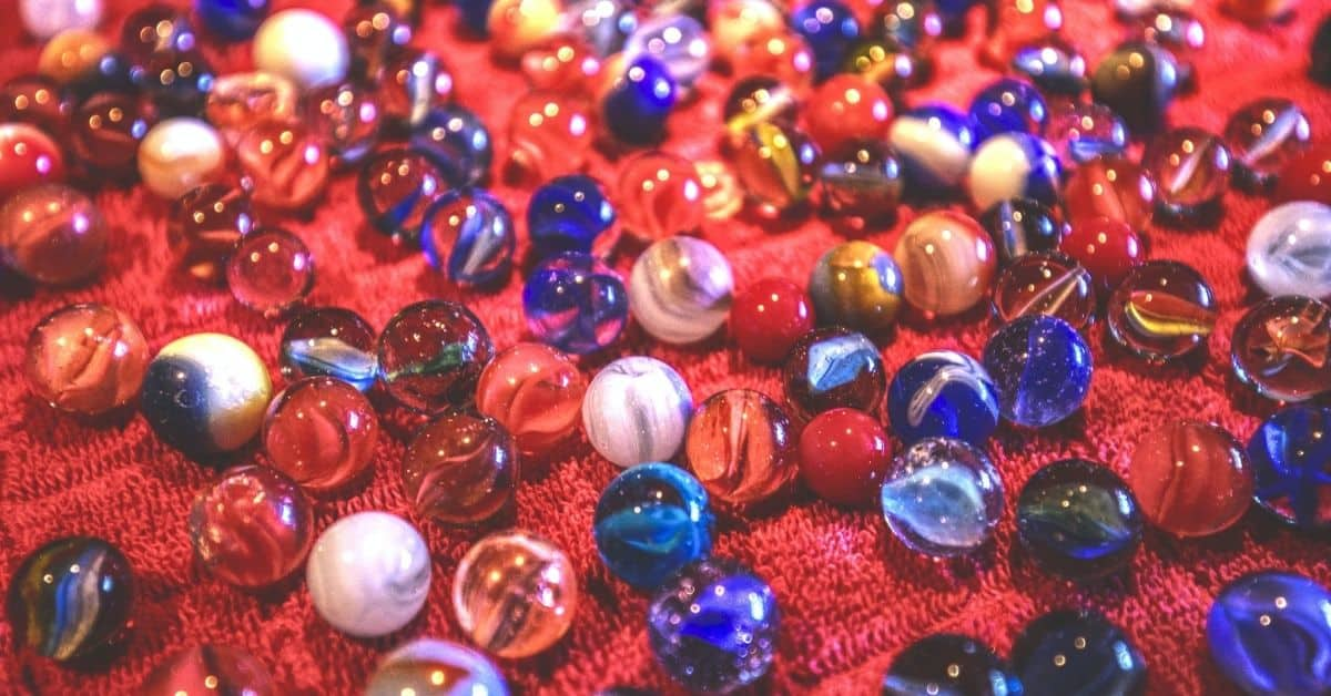 Many multicolored marbles on a red surface