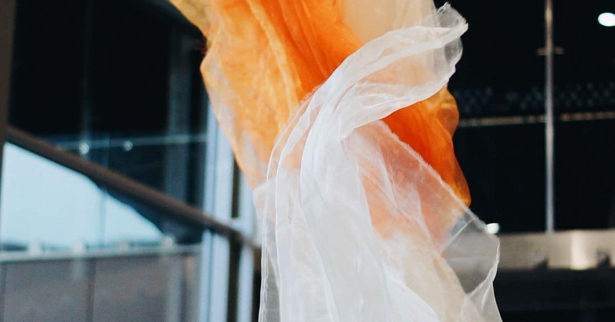 Orange and white veils blowing upward