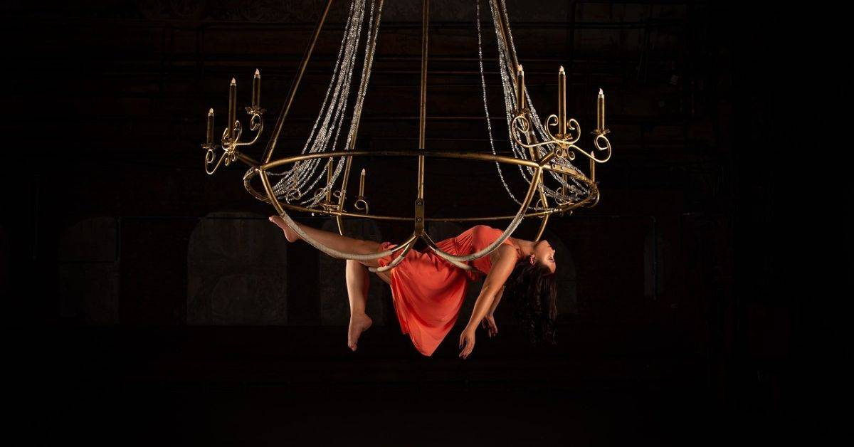 A woman in a red dress lying across an aerial hoop made to look like a chandelier