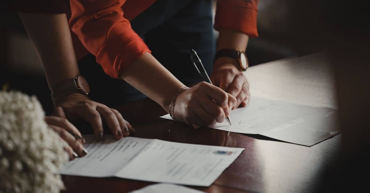 Two pairs of hands on a desk with paperwork. One person is signing a paper.