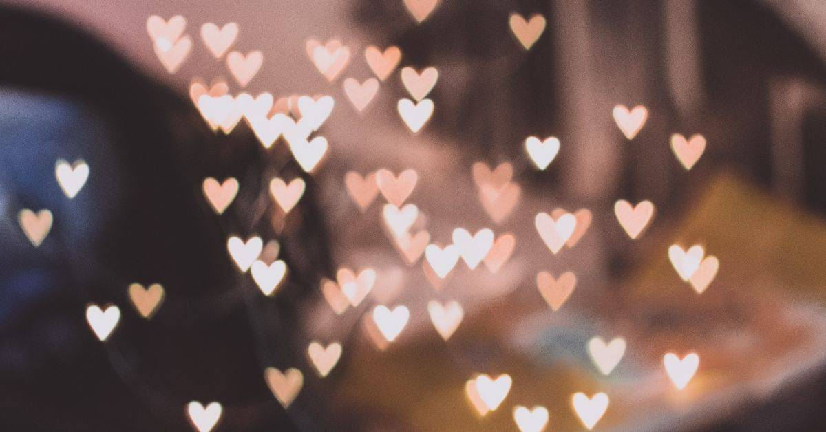 Small hearts made of pink and white light scattered across a blurred background