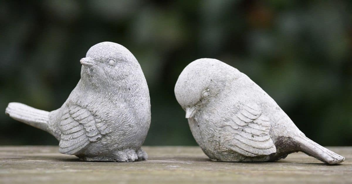 Two grey bird statues, one looking away from the other, which has it's head down.