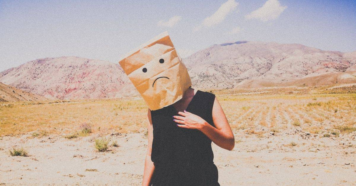 "A person in black clothes standing in a desert. They have a paper bag over their head with a rudimentary ""frowny face"" drawn on it."