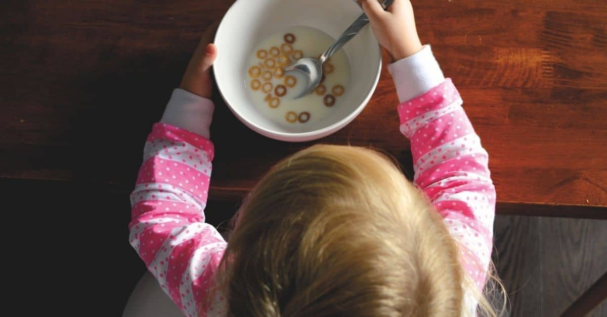 A blond haired child in a pink striped shirt sitting in front of a bowl of cereal, seen from above.