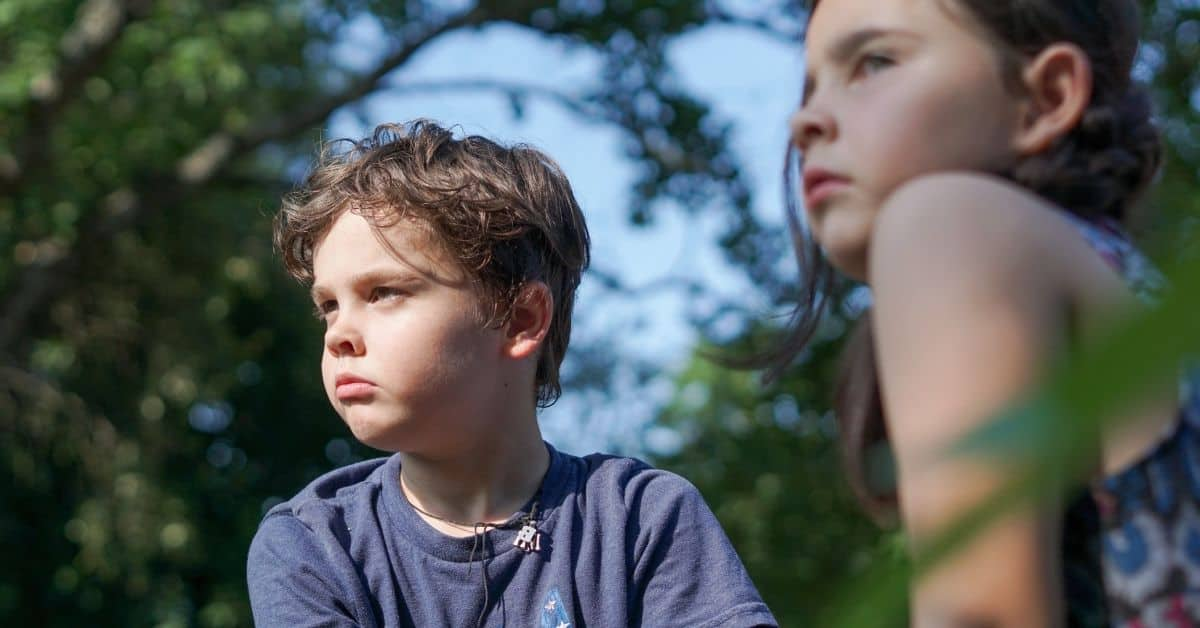 Two sullen-looking children outdoors looking away from the camera to the left.