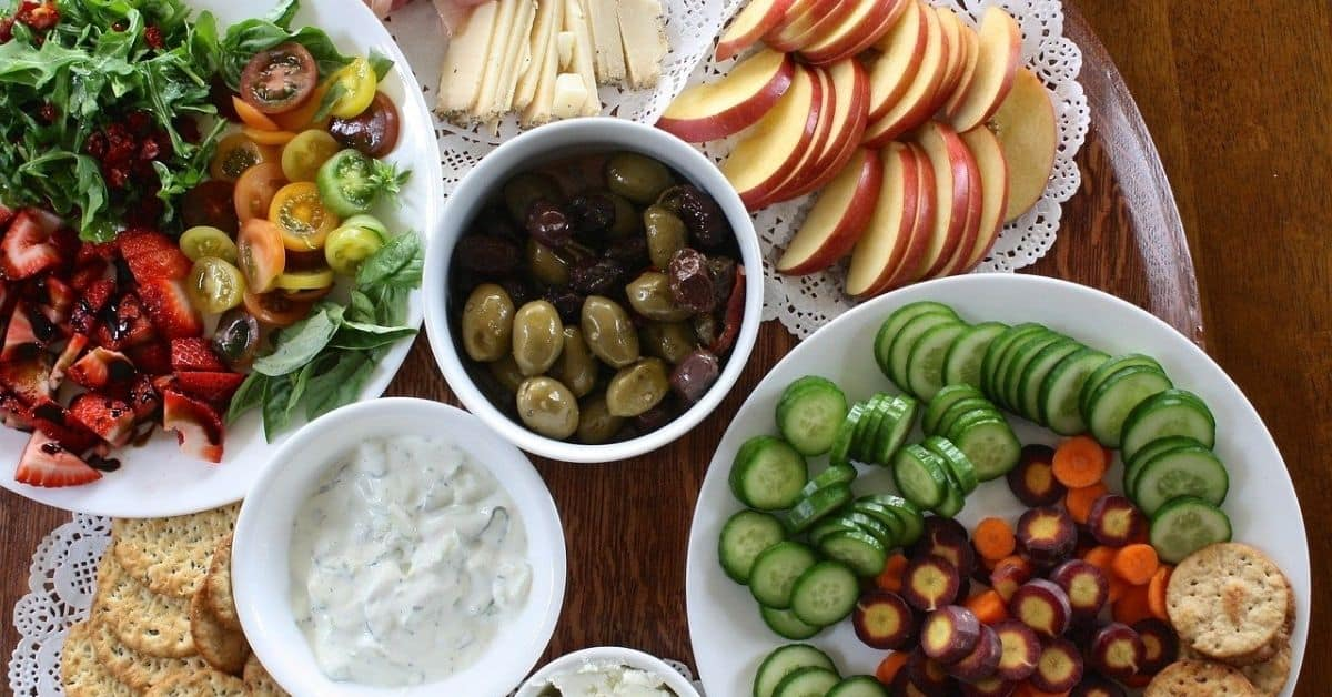 A collection of plates of various foods, including sliced fruits and vegetables, olives, salad, cheese, and meat.