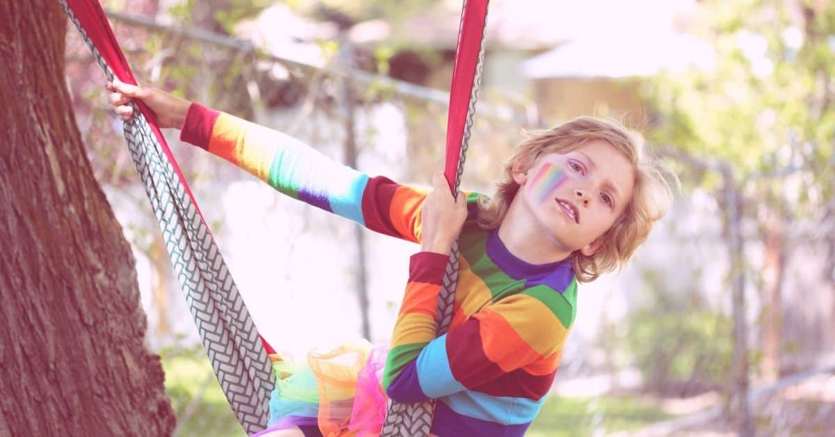 A blond haired child of indeterminate gender wearing a rainbow striped shirt and rainbow facepaint on one cheek swinging on a cloth hammock outdoors