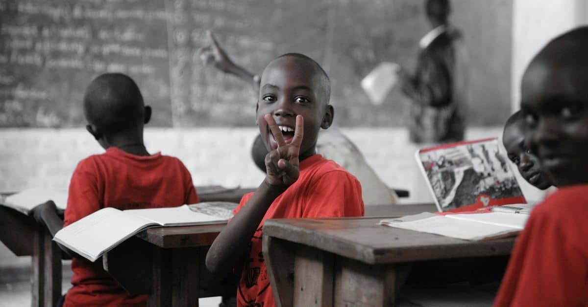 Several boys wearing red shirts in a classroom. One boy is turned away from the teacher at the blackboard, grinning and flashing a peace sign at the camera.