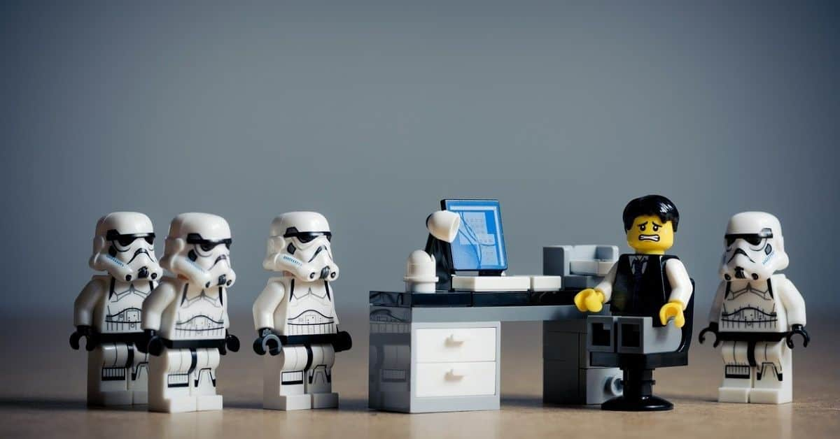 Several Star Wars Lego Stormtroopers surrounding an office worker Lego figure at a desk, who looks scared