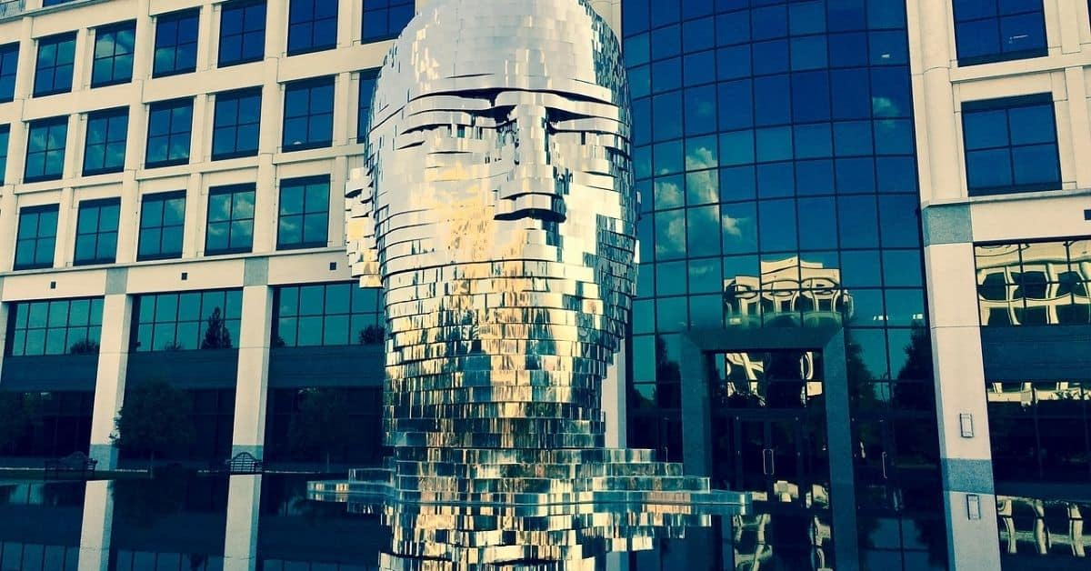 A metal sculpture of a man's head, made of moving layers