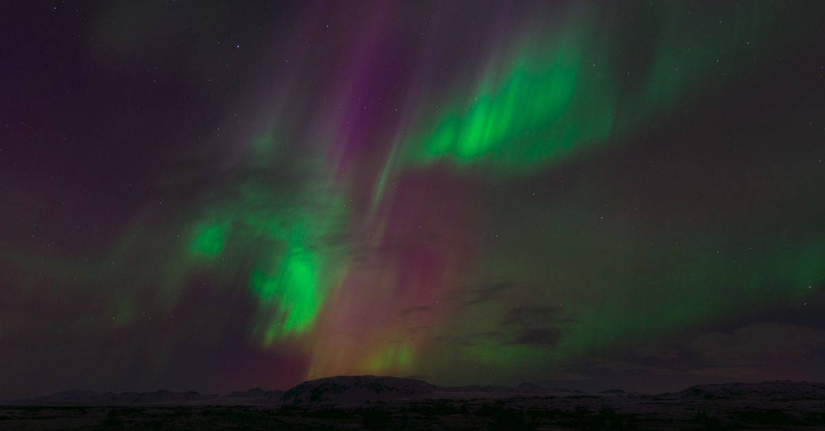The aurora borealis in shades of green and purple over a hill