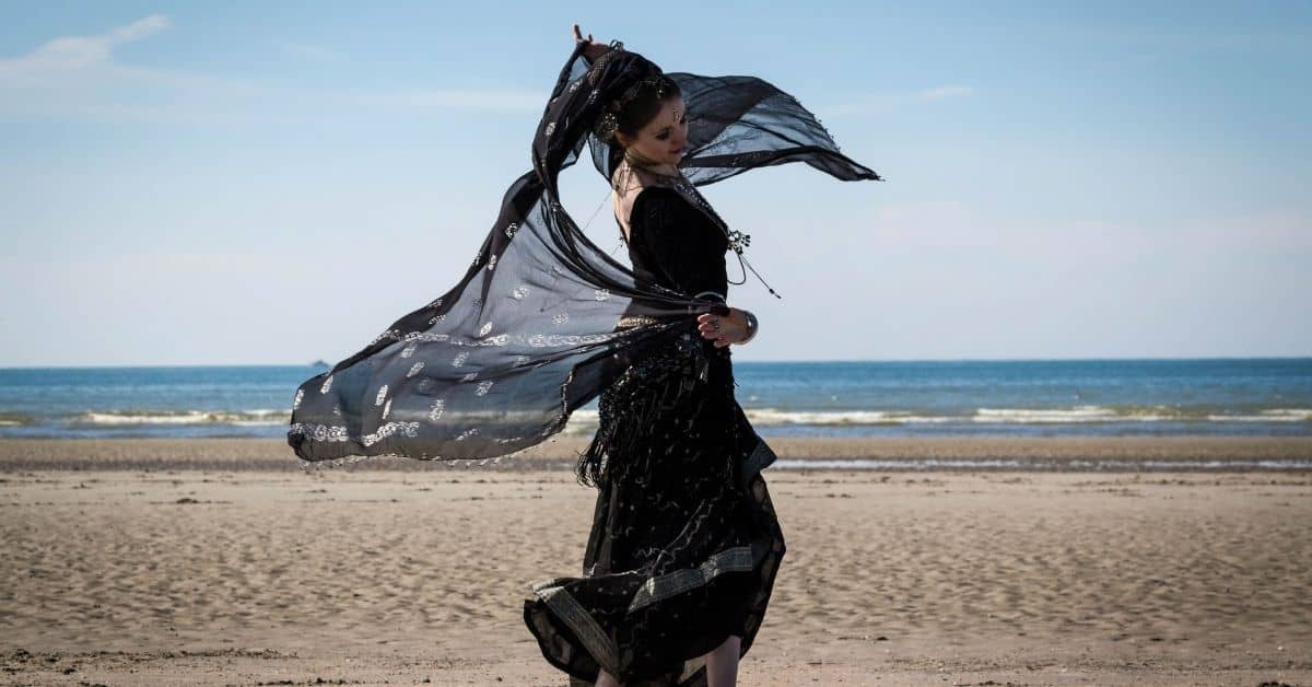 A woman dressed inblack with a black veil dancing on a beach