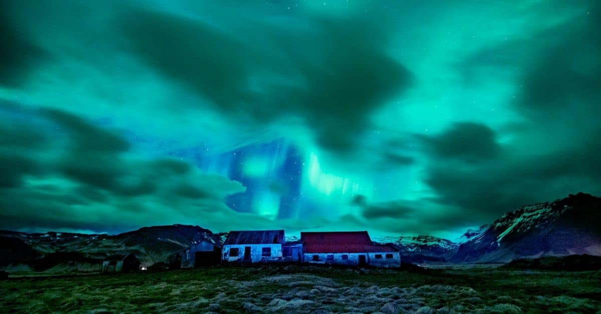 The aurora borealis in shades of teal and green over a house