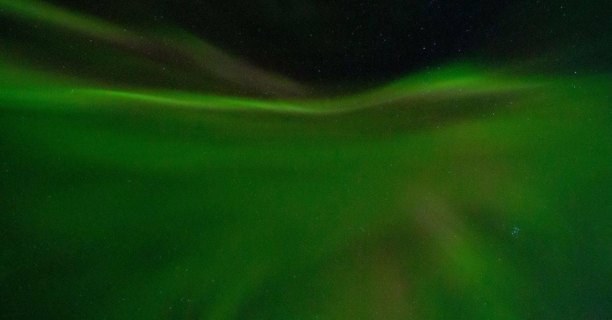 Dark green aurora borealis against a black night sky