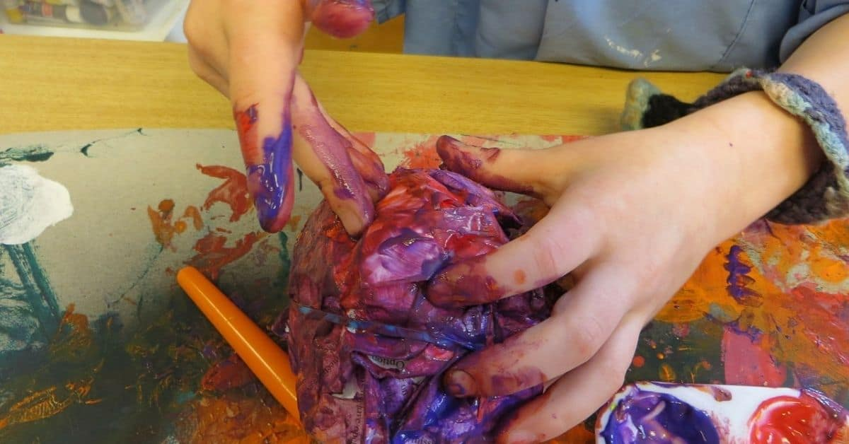 A child's hands, covered in paint, holding a rag that's also soaked with various colors of paint on a paint-stained table