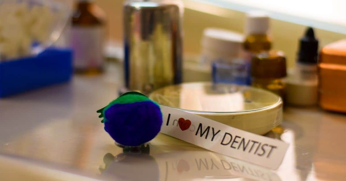 """A counter with many tools and instruments in the background. In the foreground, a blue and green ball with an attached streamer that reads """"I (heart) my dentist"""""""