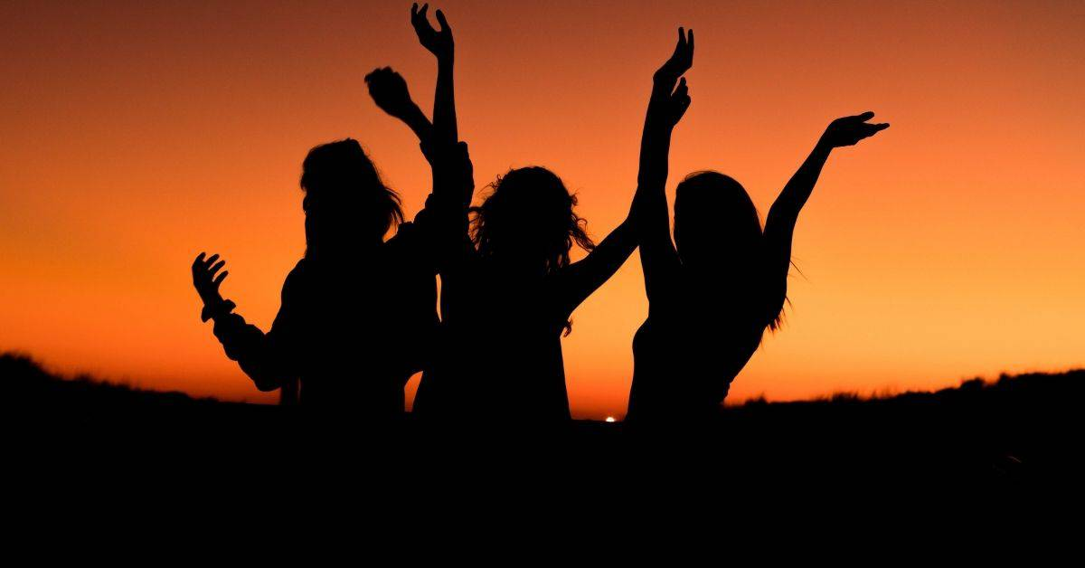 Silhouette of three people with arms raised against an orange sunset