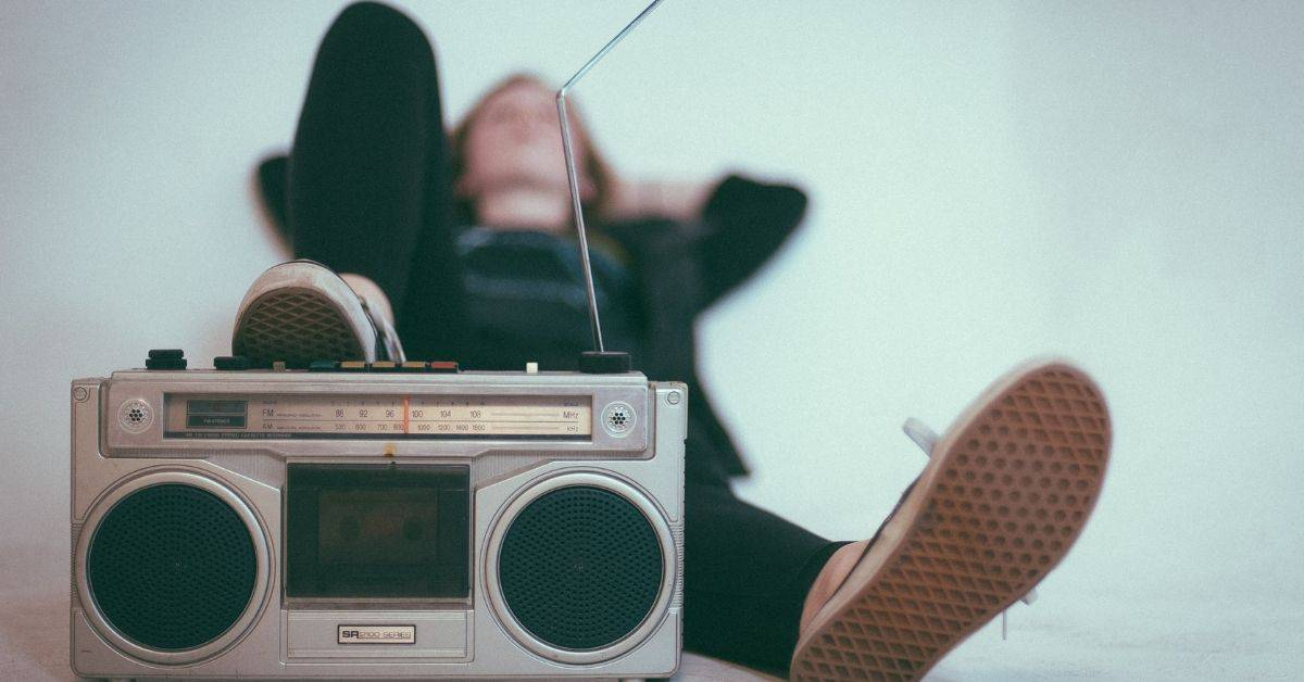 A person lying on their back in dark clothes with one foot propped up on an old radio in the foreground